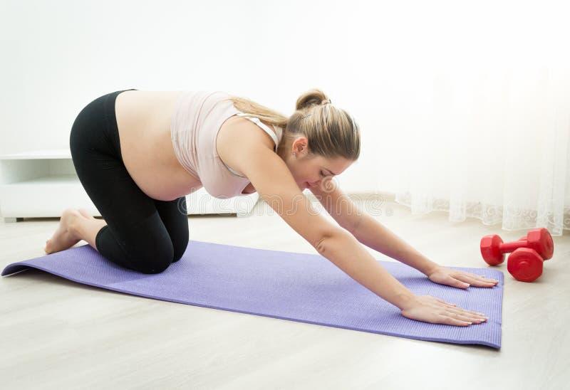 Die schwangere Frau, die Yoga tut, trainiert auf Eignungsmatte an lebendem roo stockbilder
