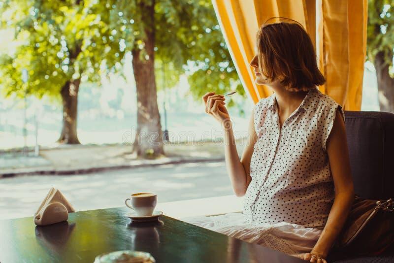 Die schwangere Frau in einem Café stockfoto