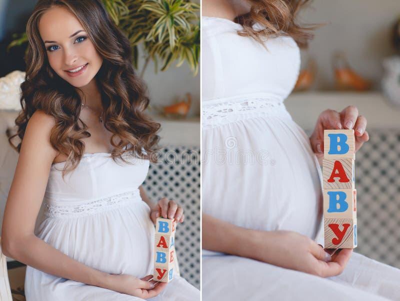 Die schwangere Frau mit Spielzeugwürfeln in den Händen stockbild