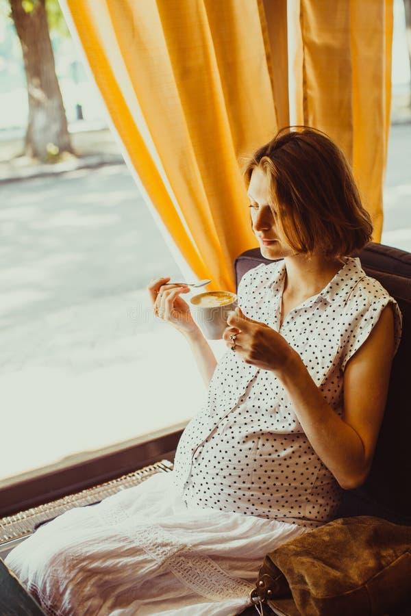 Die schwangere Frau trinkt Latte stockfotos