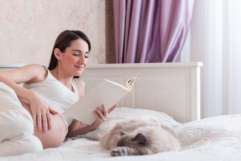 Die schwangere junge Frau las herein ein Schlafzimmer stockbilder