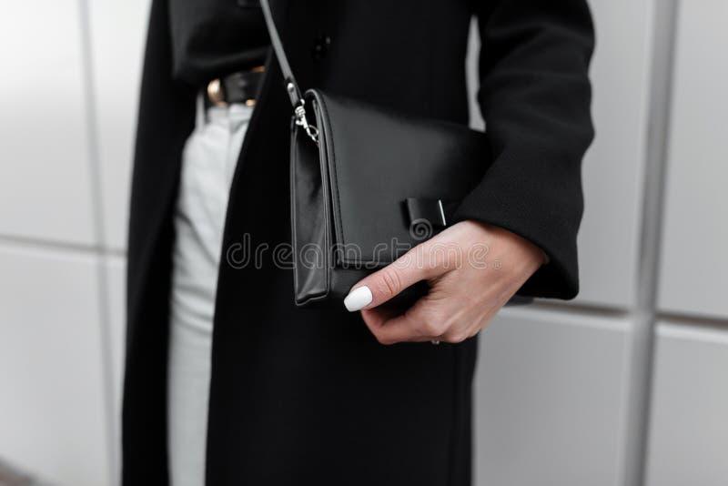 Die schwarze lederne stilvolle Tasche der modernen Frauen Modernes junges Mädchen in der stilvollen Kleidung Mode-Fr?hling-Herbst stockbild
