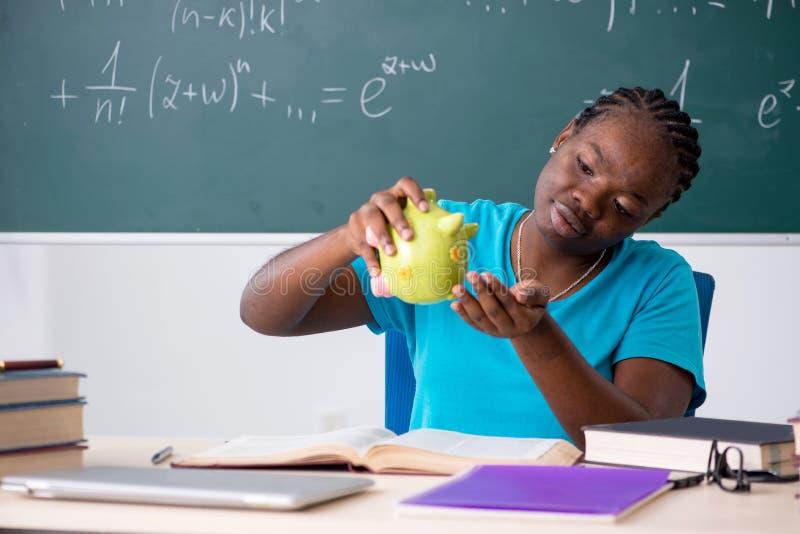 Die schwarze Studentin vor Tafel lizenzfreies stockfoto