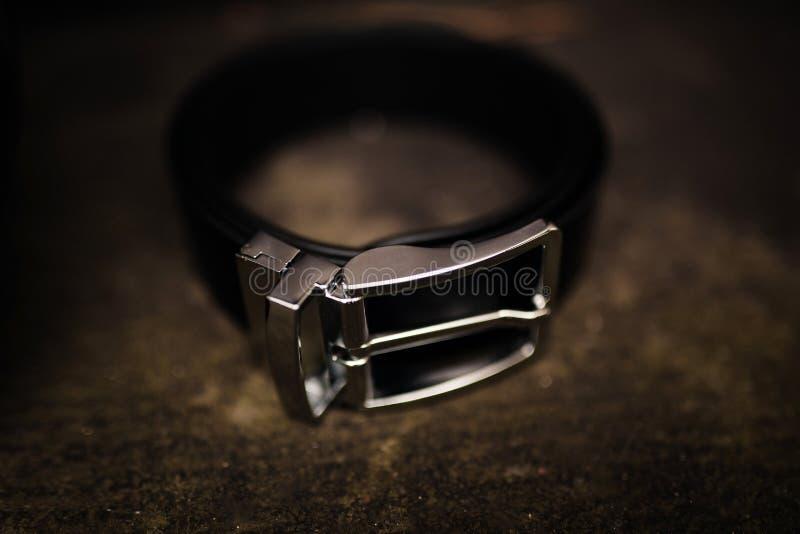 Die schwarze Uniform der M?nner f?r Hosen Schwarzer lederner Gurt Modelederg?rtel auf h?lzernem Hintergrund mit Stahlmetallschnal stockfotografie
