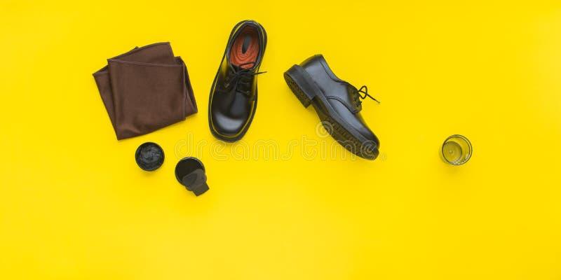 Die schwarzen klassischen Lederschuhe des Mannes mit Schuhcreme stockfotografie