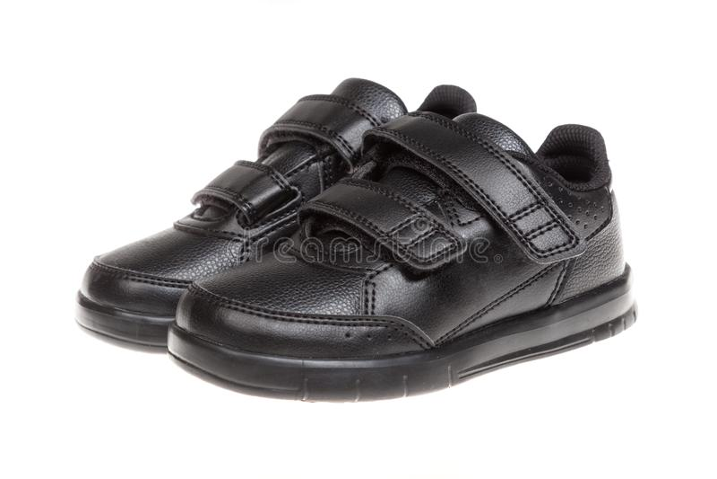 Die schwarzen Schuhe der Kinder, lokalisiert auf Weiß lizenzfreie stockfotografie