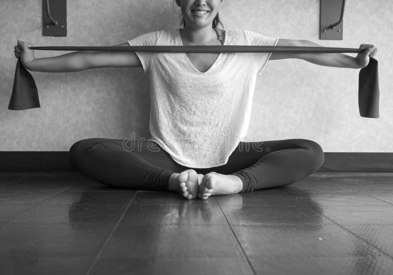 Die Schwarzweiss-Version, welche die junge aktive Frau verwendet eine theraband Übungsbande, um ihre Arme zu verstärken ofSmiling lizenzfreie stockfotografie