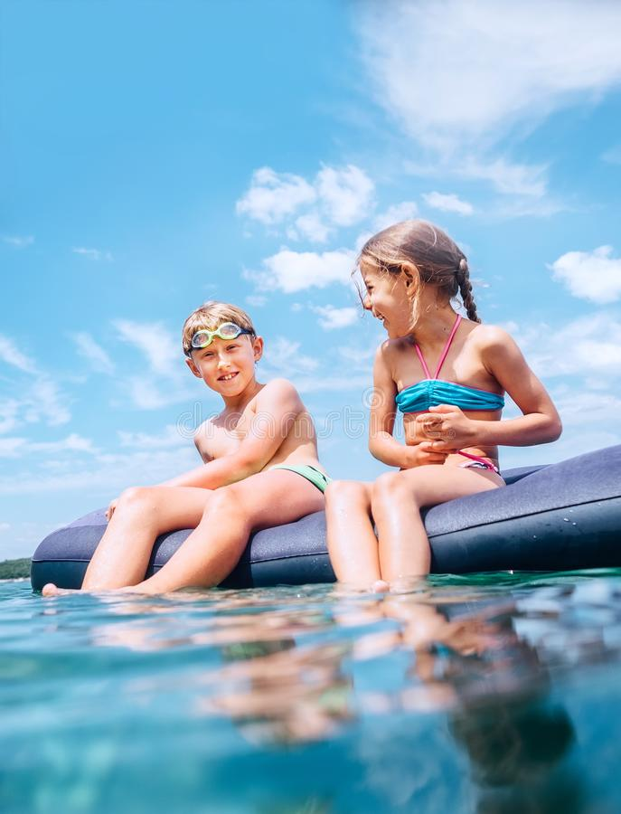 Die Schwester und Bruder, die auf aufblasbarer Matratze sitzen und das Meerwasser genie?en, haben Spa? wenn Schwimmen im Meer Unv lizenzfreies stockbild
