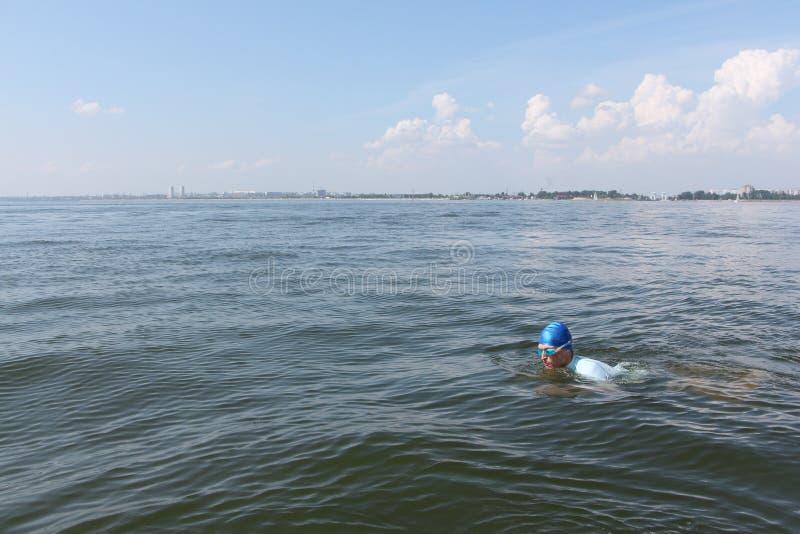 Die Schwimmen des jungen Mannes im Fluss lizenzfreies stockbild
