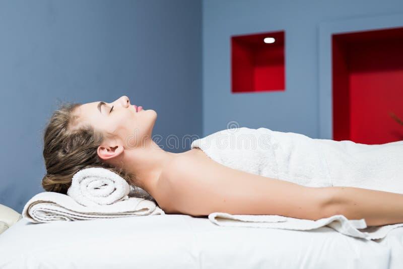 Die Seite, die oben von einer lächelnden Frau sich entspannt auf einem Ruhesessel mit Augen nah ist, schloss in einer Wellnessmit stockfoto