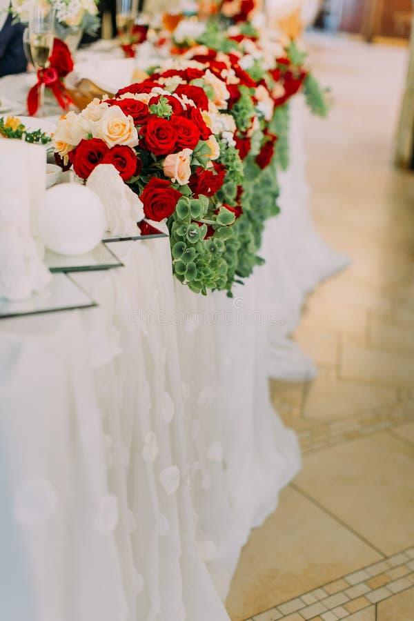 Die Seitenansicht der Nahaufnahme der roten und weißen Rosen verzieren die Hochzeitstafel lizenzfreies stockfoto