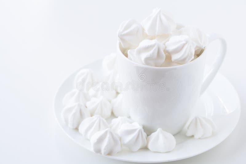 Die Seitenansicht der weißen Meringe in der weißen Teeschale stockbilder