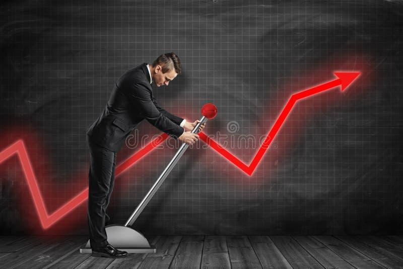 Die Seitenansicht des Geschäftsmannes unten schauend und großen Hebel nahe schwarzem Diagramm ziehend ordnete Wand mit rotem Diag lizenzfreie stockfotos