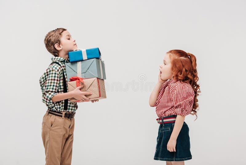 die Seitenansicht des Jungen Geschenke darstellend entsetzte kleines Mädchen lizenzfreies stockbild
