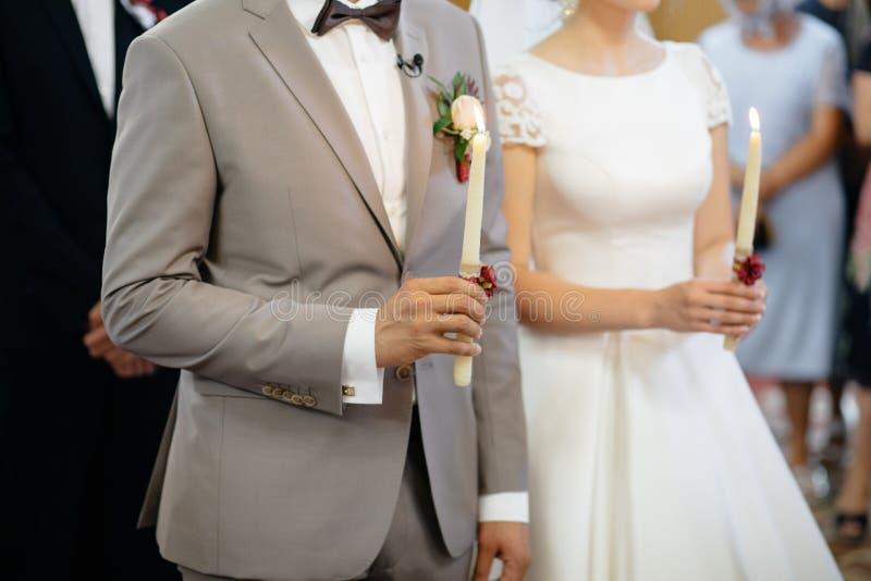 Die Seitenansicht des Jungvermählten ` übergibt das Halten des Kerzen wrappe stockfotografie