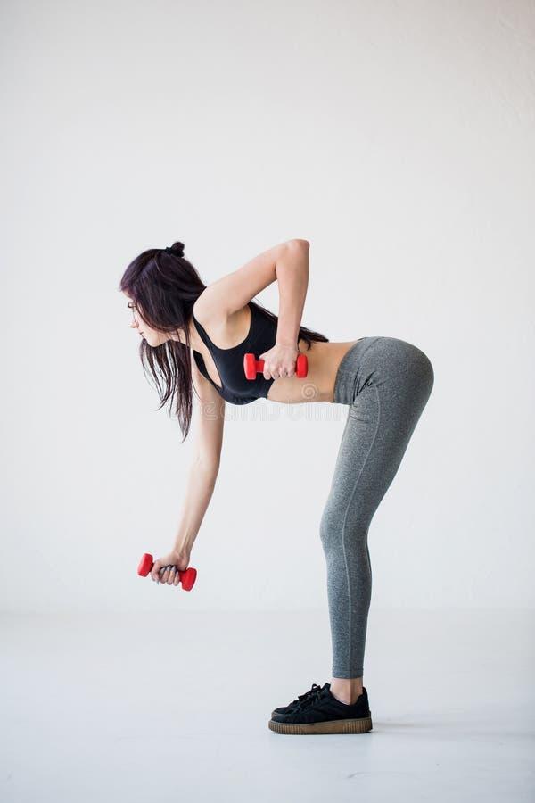 Die Seitenansicht in voller Länge des Ausarbeitung des athletischen Brunette, der Übungen mit den Dummköpfen tut Studiostandort lizenzfreie stockfotografie