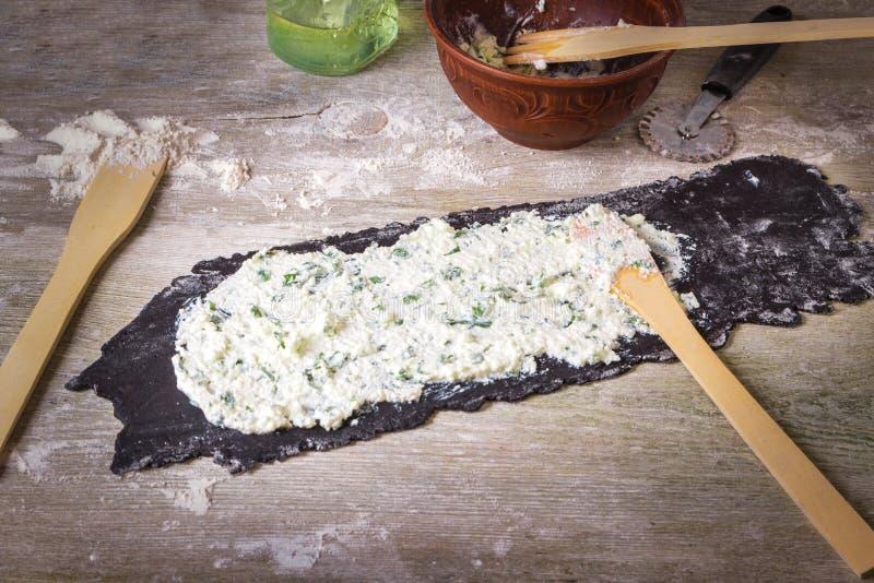 Die selbst gemachte faule rohe schwarze Kopffüßertinten-Teigwarenravioli kochen angefüllt mit Käse und Petersilie auf einem h stockfotografie