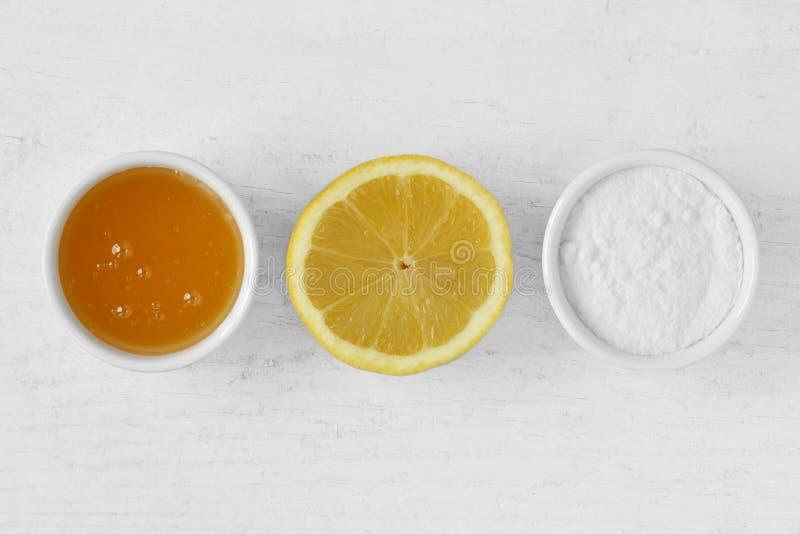 Die selbst gemachte Gesichtsmaske, die aus Honig heraus gemacht werden, der Zitronensaft und das Backen belegt mit Rasen stockbild