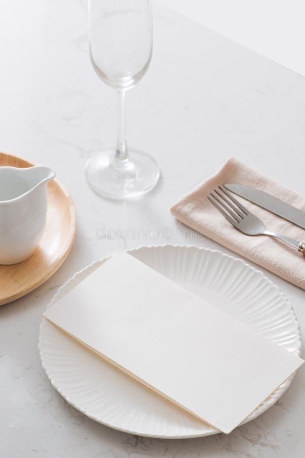 Die Serviette auf der Platte Weiße Platten, Gabel, Messer auf grauer Steinplatte lizenzfreies stockbild