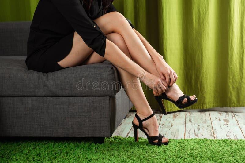 Die sexy Beine der Frauen Frau kn?pft ihre Schuhe des hohen Absatzes Sch?nheitsbeine, die Kleid mit Schuhen des hohen Absatzes tr lizenzfreies stockfoto