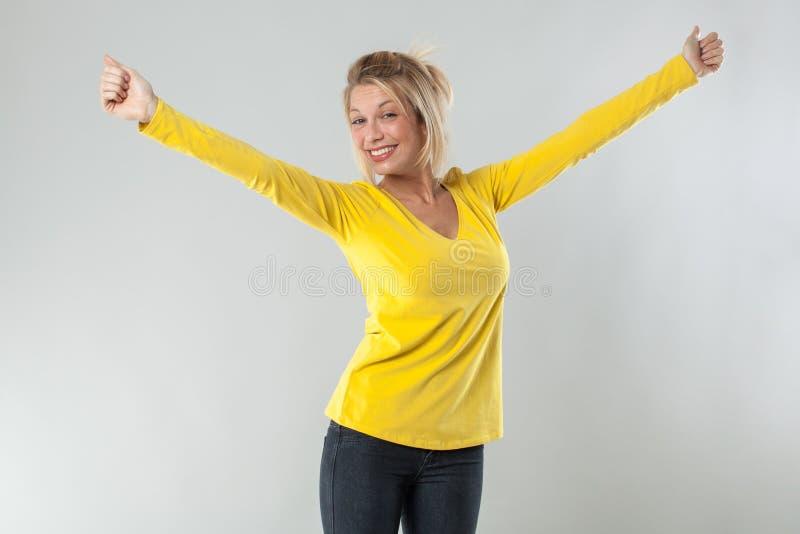 Die sexy blonde Frau 20s, die mit den Armen lächelt, öffnete sich für Freude stockbilder
