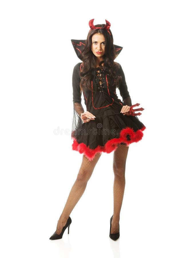 Die sexy Frau, die Teufel trägt, kleidet, Double mit gespreizten Beinen und hält Dreizack stockfotos