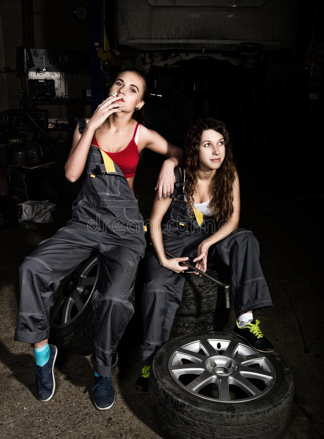 Die sexy Mädchen der müden Mechaniker, die auf einem Stapel von Reifen auf Reparaturen eines Autos, eins der Mädchen sitzen, rauc stockfoto