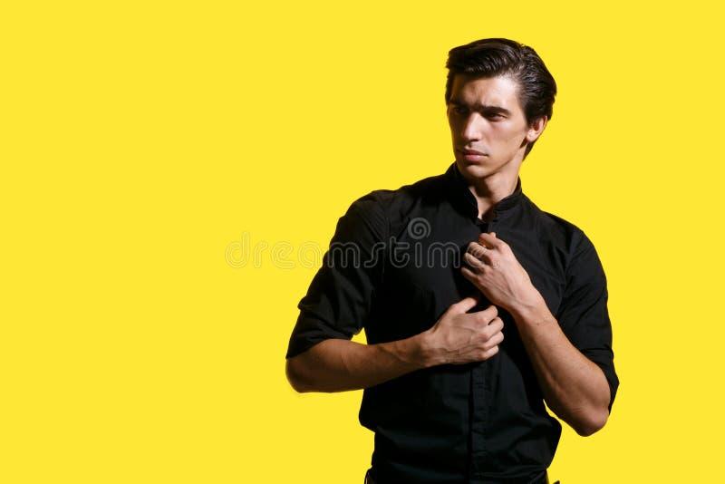 Die sexy männlichen Modelle, lokalisiert auf einem gelben Hintergrund, aufwerfend im Studio, vereinbart sein schwarzes Hemd mit d lizenzfreie stockfotografie