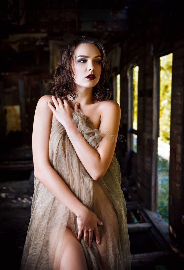 Die sexy schöne junge Frau, die im Stoff bedeckt wird, steht im alten Zuglastwagen stockbilder