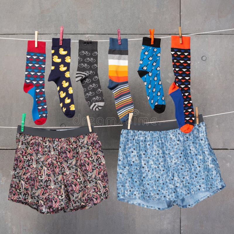 Die Socken und die Unterhosen vieler Männer hängen an den Wäscheleinen, als ob, trocknend, das Konzept einer Zusammenstellung, ge lizenzfreies stockfoto