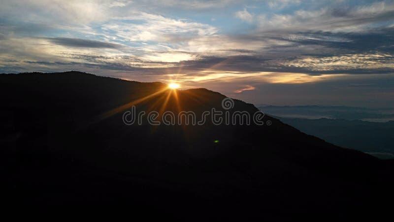die Sonne, die hinter dem Berg erscheint lizenzfreie stockfotografie