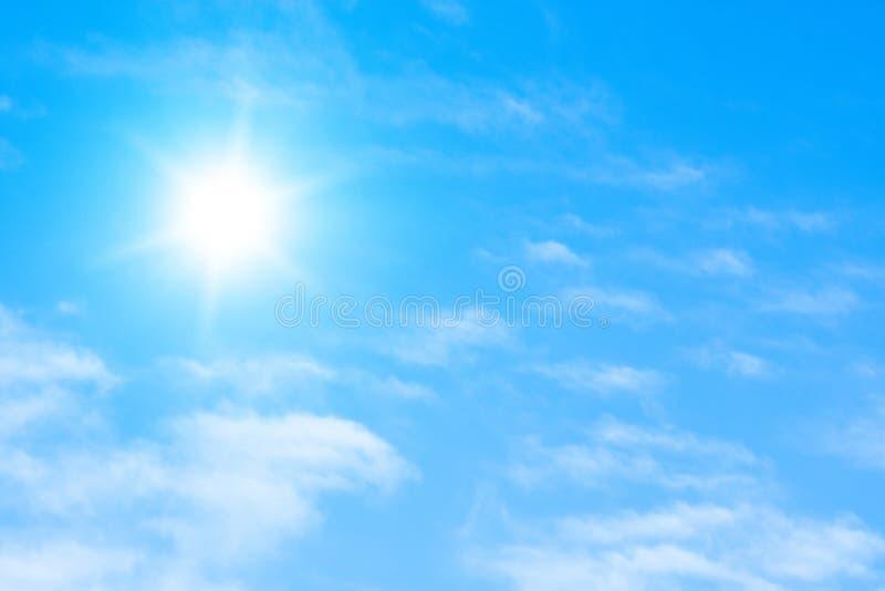Die Sonne mit hellen Strahlen im blauen Himmel mit weißem Licht bewölkt sich stockbild