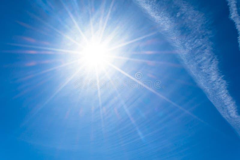 Die Sonne mit hellen Strahlen im blauen Himmel mit weißes Licht Contrail bewölkt sich von den Flugzeugen lizenzfreie stockfotografie