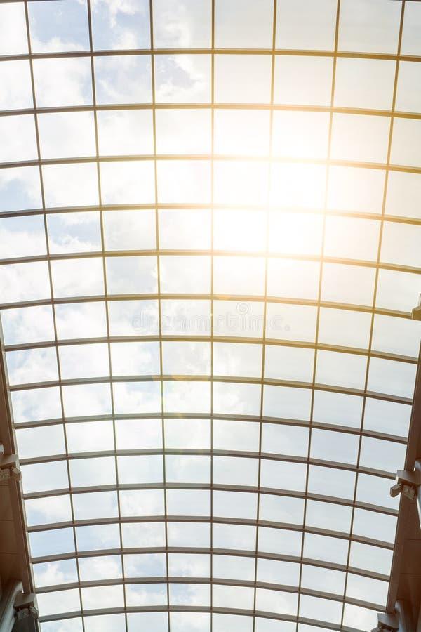 Die Sonne ` s Strahlen glänzen durch das Glasdach des Einkaufszentrums Schöner moderner Architekturhintergrund Blauer bewölkter H stockbild