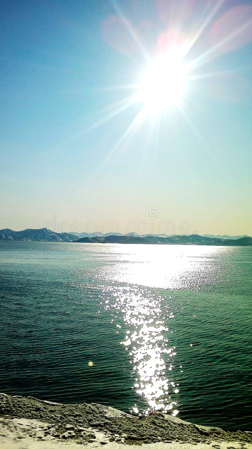 Die Sonne an seinem Zenit über der Kamchatka-Bucht lizenzfreies stockbild