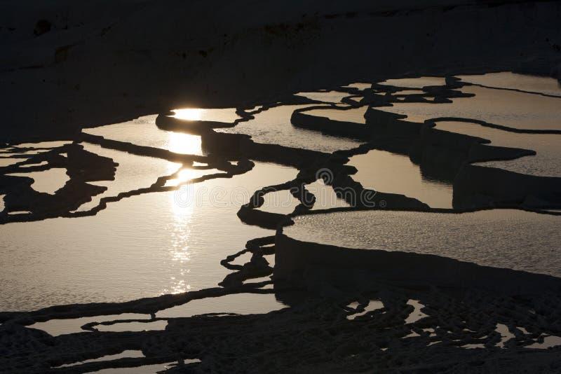 Die Sonne stellt über die ausgezeichneten Travertine ein, als Baumwollschloss bei Pamukkale in der Türkei andernfalls bekannt lizenzfreies stockfoto