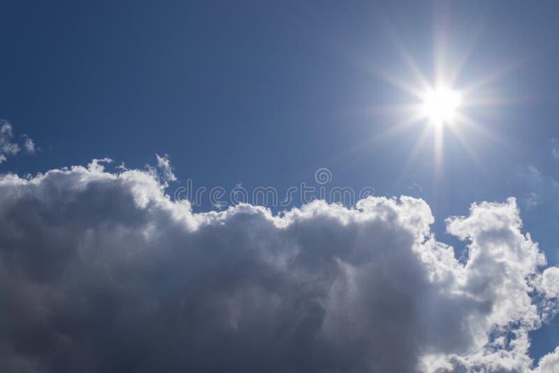 Die Sonne und eine weiße Wolke im blauen Himmel an einem schönen Sommertag als Hintergrund lizenzfreies stockfoto