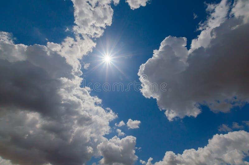Die Sonne zwischen den Wolken im blauen Himmel stockfoto
