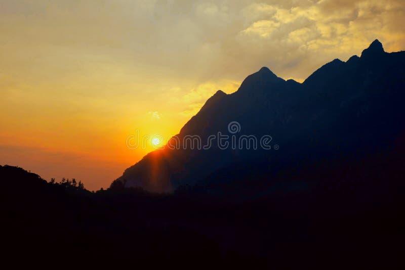 Die Sonnenaufgänge vom Gebirgshorizont und glüht gelb stockbild