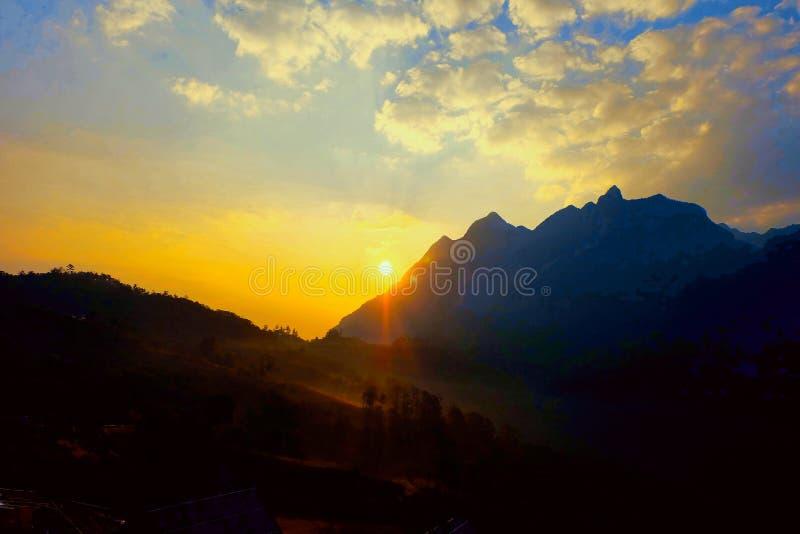 Die Sonnenaufgänge vom Gebirgshorizont und glüht gelb stockfotografie