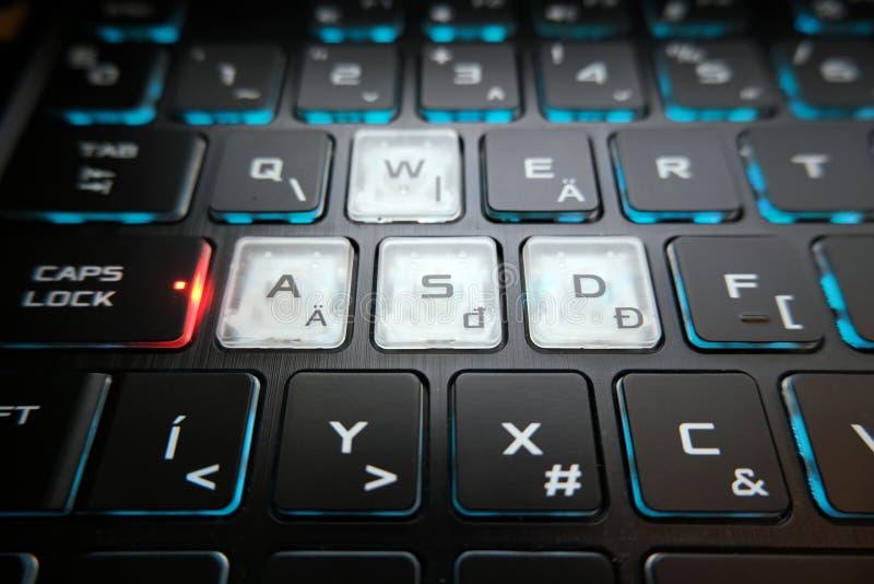 Die Spieltastatur glänzt mit mehrfarbigen Schlüsseln, asdf Knöpfe in der Mitte stockfotos
