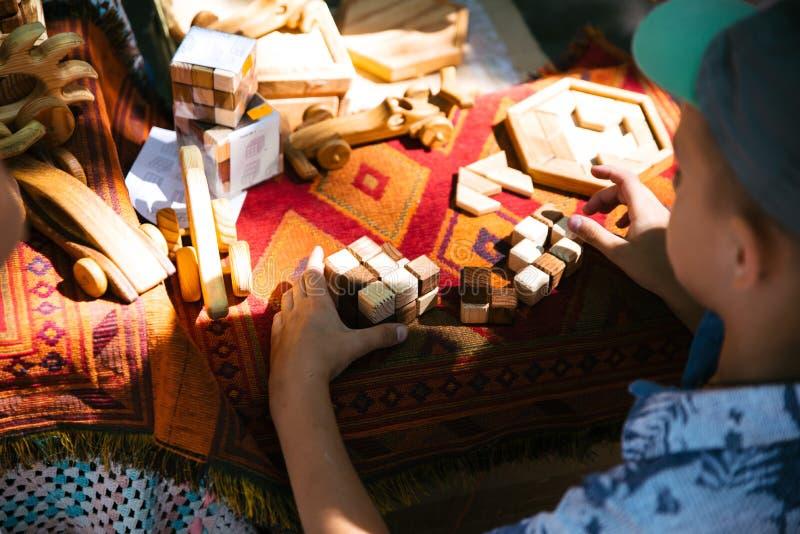Die Spielwaren der hölzerne Kinder auf der Natur Junge, der Würfel spielt stockbilder