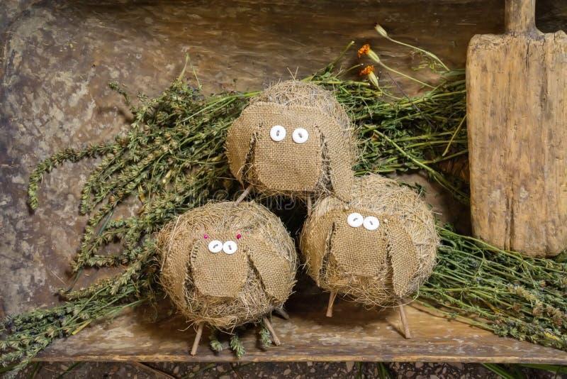 Die Spielzeugschafe, die vom Stroh und vom Stoff gemacht werden, stehen auf gemähtem Gras stockfotografie