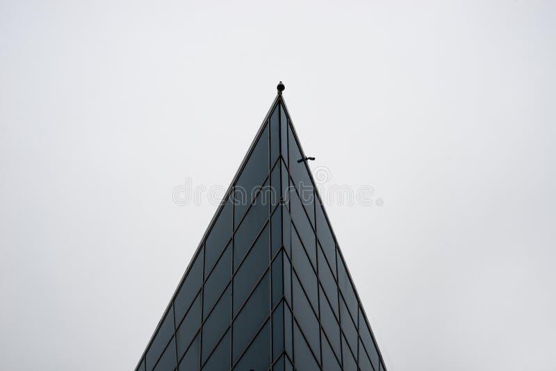 Die Spitze eines hohen Gebäudes mit einer Überwachungskamera stockfotografie