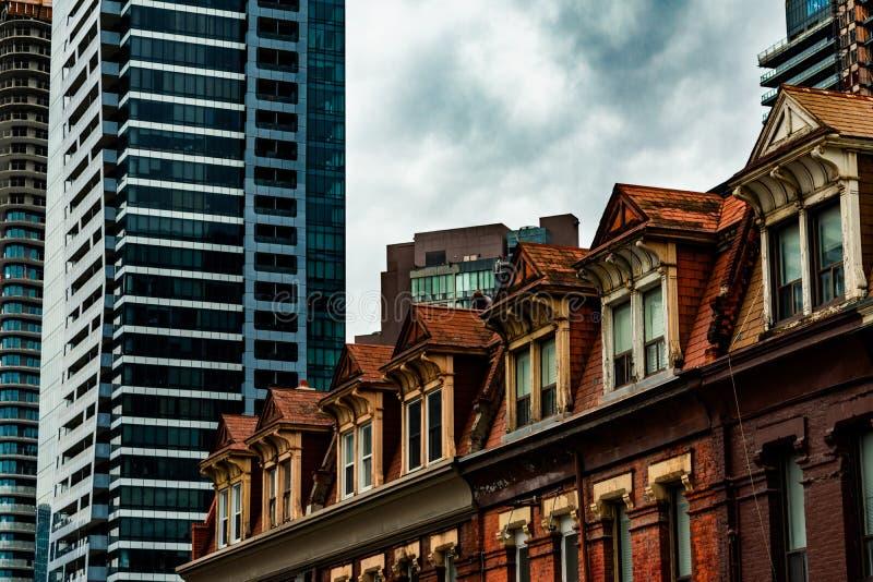 Die Spitzen von den alten Backsteinbauten umgeben durch Wolkenkratzer in im Stadtzentrum gelegenem Toronto stockfotografie