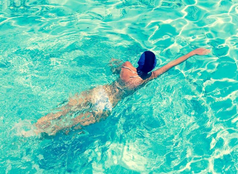 Die Sport- Frau schwimmt im hellen blauen Wasser stockfotografie