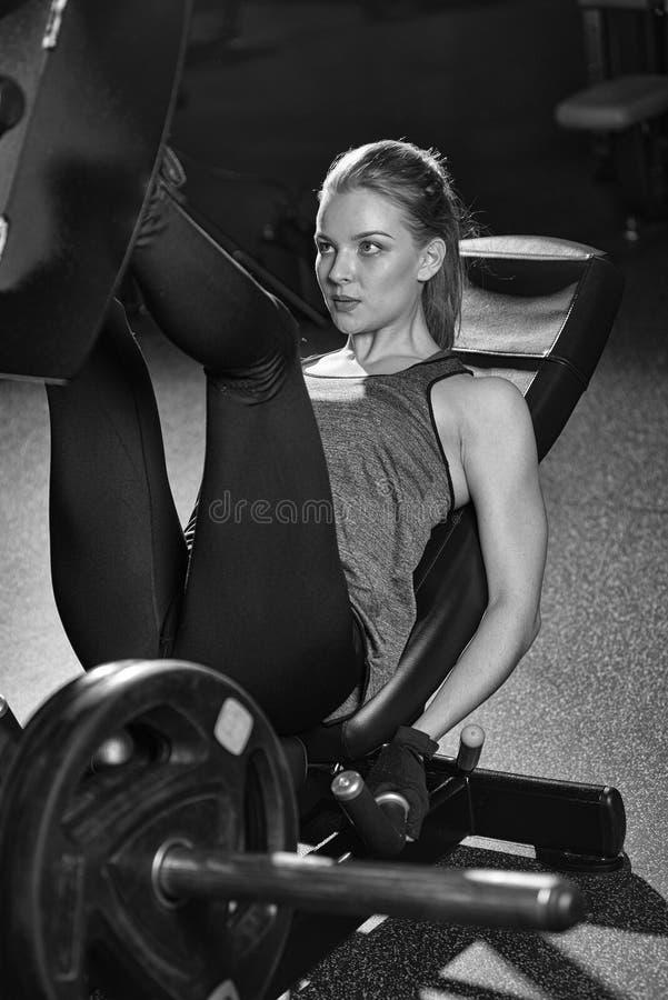 Die sportive Frau, die Gewichte verwendet, bedrängen Maschine für Beine Gymnastik stockfoto