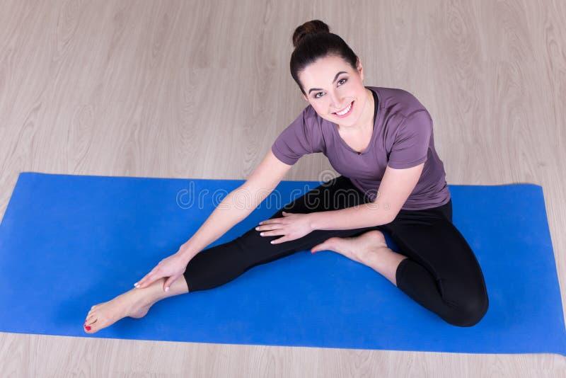 Die sportliche Frau, die das Ausdehnen tut, trainiert auf dem Boden lizenzfreie stockfotografie