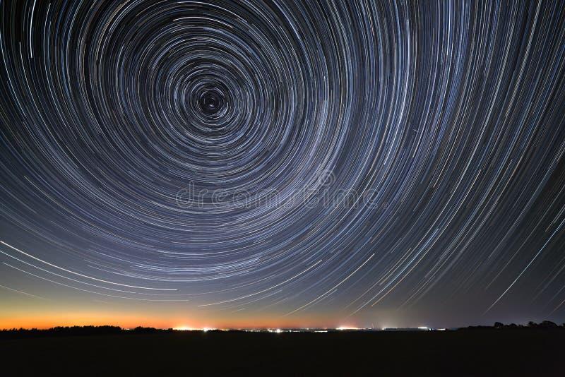 Die Spur von Sternen im nächtlichen Himmel wird im Fluss reflektiert Bewegung im Raum fotografiert auf langer Belichtung lizenzfreie stockbilder