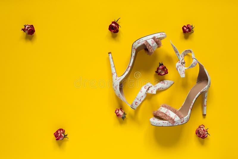 Die Stöckelschuhe der Sommerfrauen Rosa Flamingos und Federn Kleine rote Rosen Gelber Papierhintergrund lizenzfreie stockfotografie